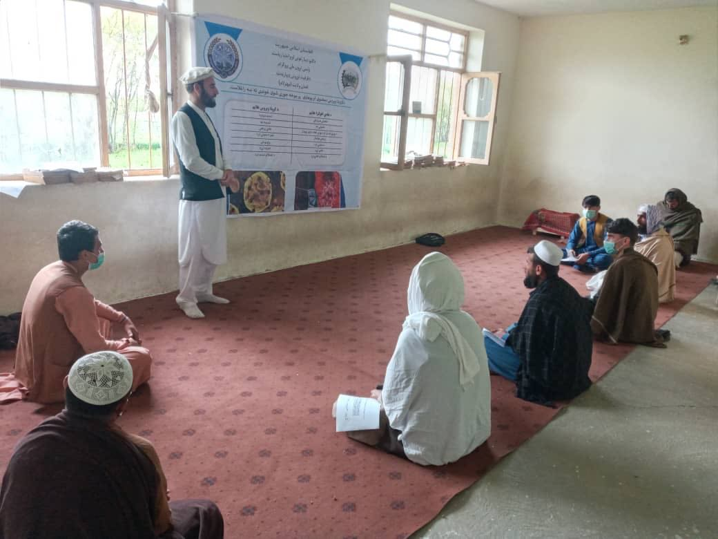 A World Bank project staff raising awareness among rural Afghans on COVID-19