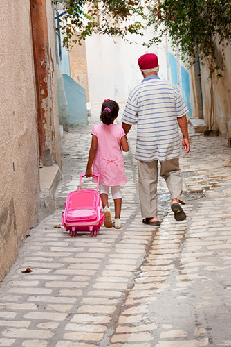 Lyubov Timofeyeva | Shutterstock.com - Grandfather and granddaughter walking back from school in Sousse, Tunisia