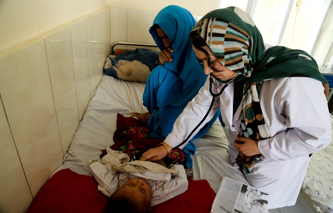 A doctor is examining a young child suffering from pneumonia in Dehadi District Hospital, northern Balkh Province