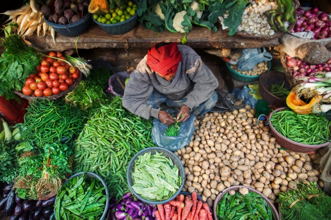 A man surrounded by vegetables and greens in an Indian Bazaar.