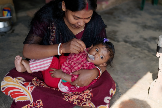 Indian Bengali tribal mother is feeding her baby on her lap in a rural background. Indian rural lifestyle