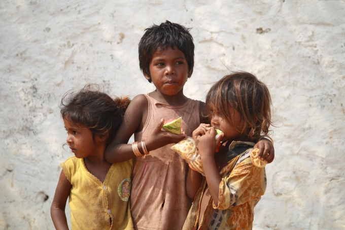 Poor Indian girls on the street eating a piece of watermelon.