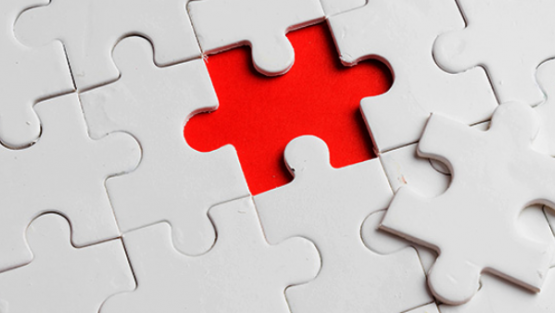 Image of a jigsaw puzzle with a middle piece displaced.