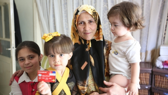A refugee family living in Southeast Turkey is among the beneficiaries of the Emergency Social Safety Net program. One of the children is holding the card they use to access the cash transfers. Photo: © Deniz Akkus/World Food Programme