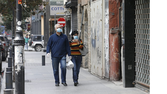 People walk along the streets with masks.