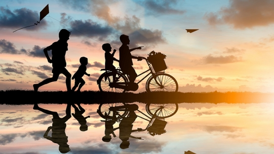 Children riding bikes and chasing paper airplanes and kites at sunset