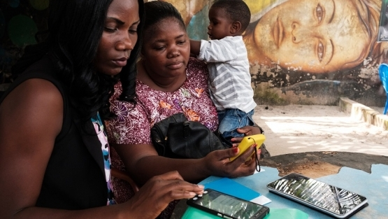 Two women use a mobile money payment device in Abidjan, Côte d'Ivoire. Photo: © Nyani Quarmyne/International Finance Corporation