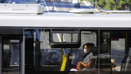 A woman is seen through the window of a public bus wearing a face mask to protect her from COVID-19 in downtown Sao Paulo, Brazil. Photo: © Nelson Antoine/Shutterstock