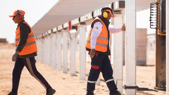 Workers install metal posts at a solar park in Egypt. © Dominic Chavez/IFC