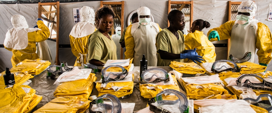 Health workers put their Personal Protective Equipment on before entering the zone where people suspected of having Ebola are held in quarantine to be monitored and treated at the Ebola Transition Center. © Vincent Tremeau/World Bank