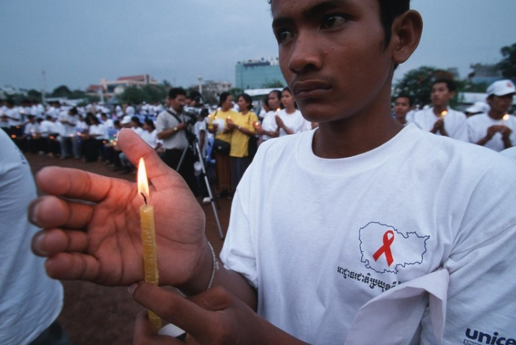 A campaigner holds a candle for people who have died of AIDS at a rally