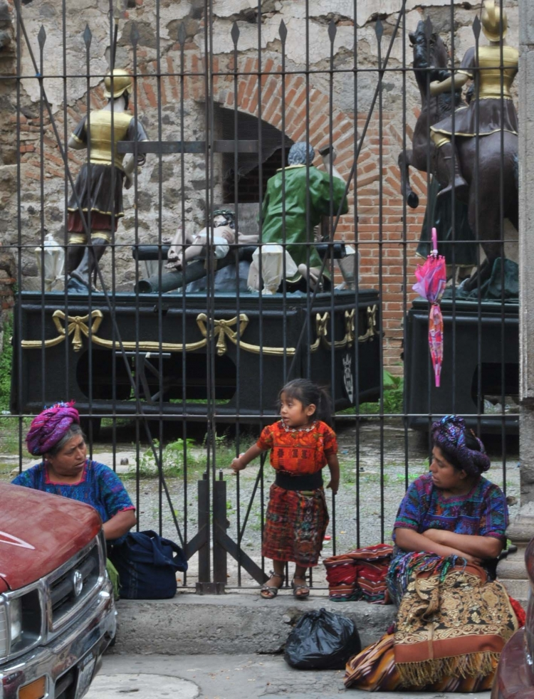 Artisans rest near a couple of pasos, the religious wooden statues used during the Easter processions