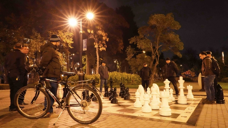 Fuad observing citizens playing chess in the central park of Baku