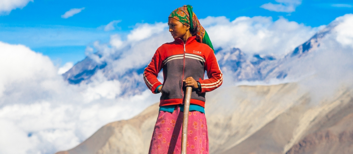 Local women is standing in the mountains holding a shovel.