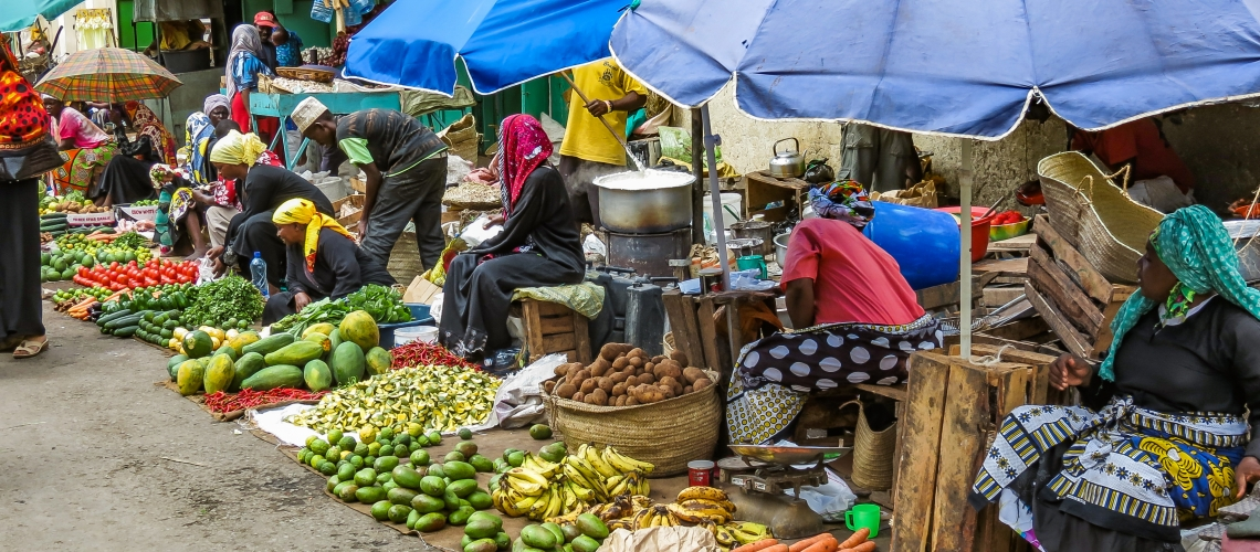 Mombasa, Kenya: Group of poor women selling vegetables and fruits on a street