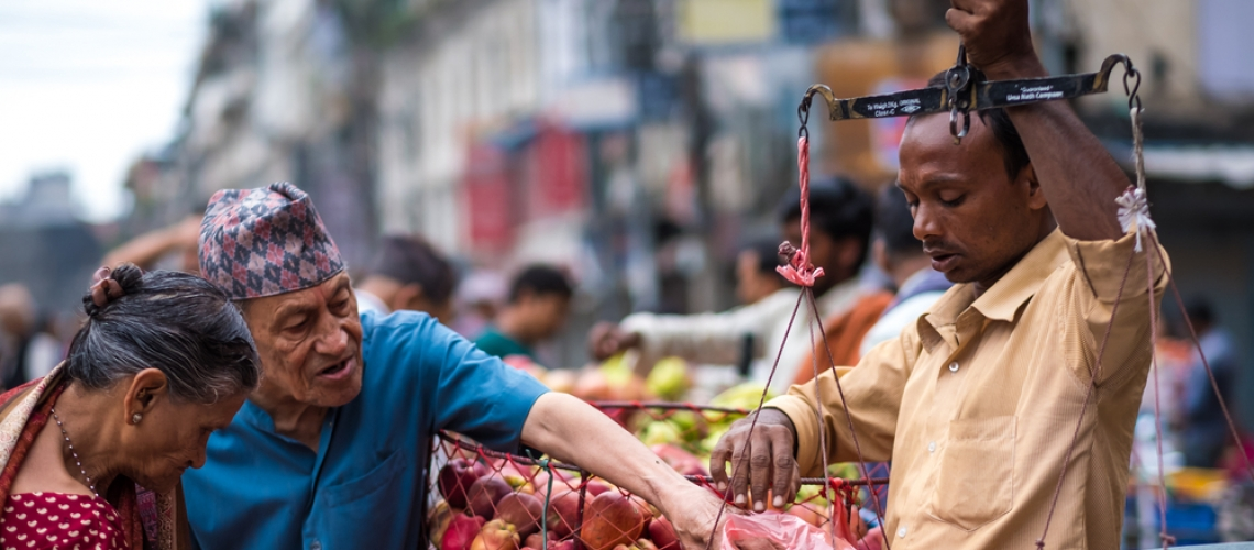 Nepalese man weighs up apples for older people on the local street market in Kathmandu, Nepal. Photo: Shutterstock