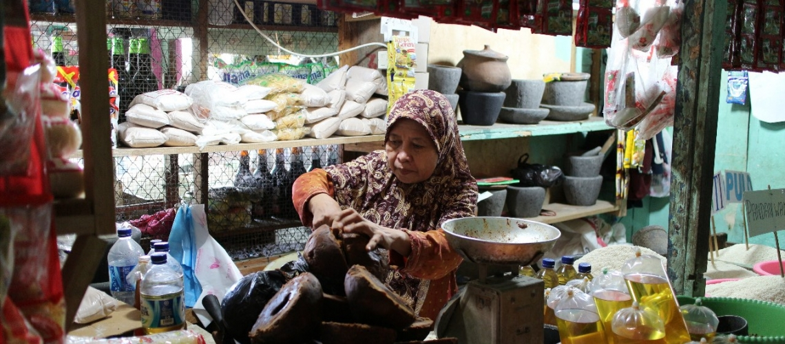 An Indonesian lady is preparing to sell household items in a traditional market. Photo: Jerry Kurniawan/World Bank