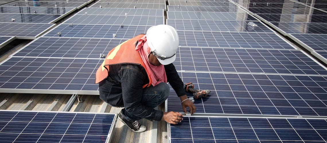 A technician installs solar panels on a factory roof in Bangkok, Thailand.