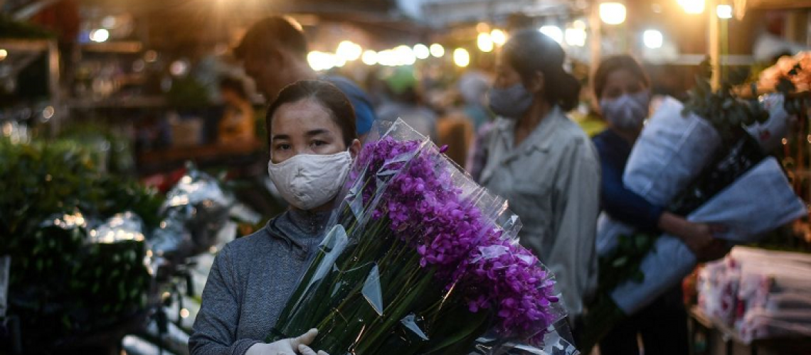 A woman wearing a face mask amid concerns over the spread of COVID-19 (coronavirus) carries flowers at the Quang Ba flower market in Hanoi at dawn on May 11, 2020. (Photo by MANAN VATSYAYANA/AFP via Getty Images)