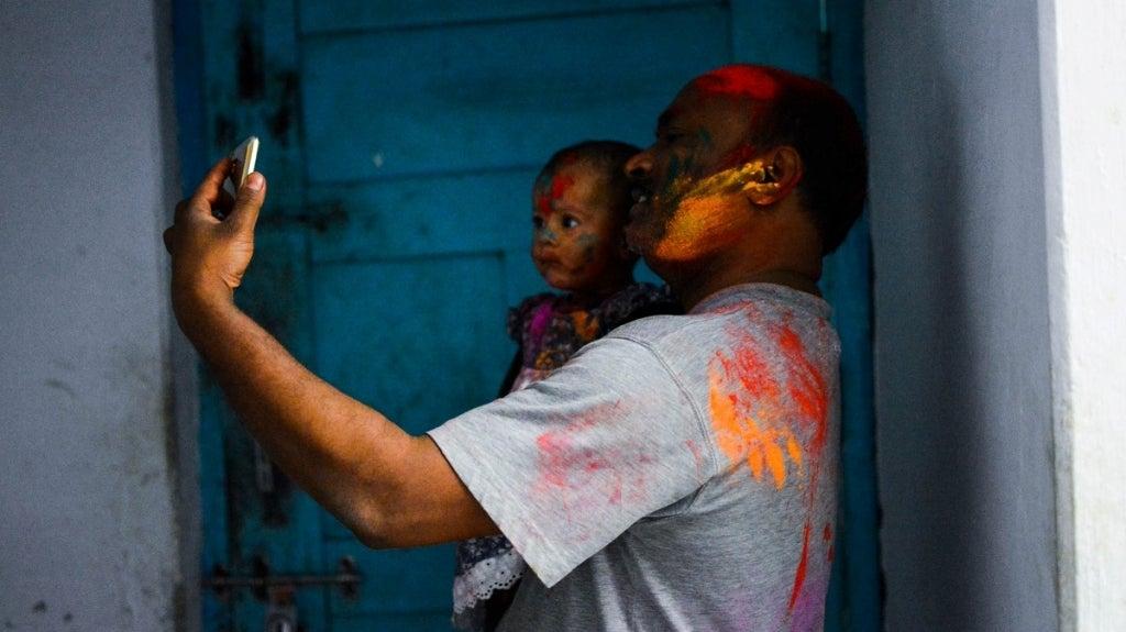 Young father taking a selfie with his child, India. Photo: Vishnu Nishad/Unsplash