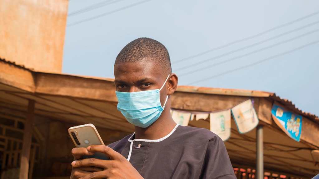 Smartphone user with a mask. Photo: Vic Josh/Shutterstock