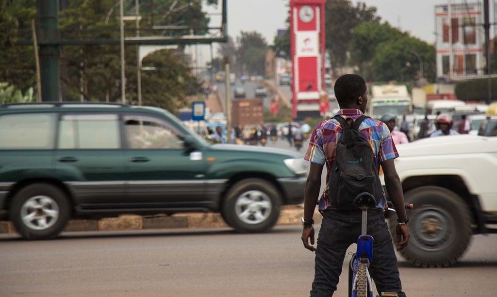 Young man on a bicycle waiting at a road junction in Kampala, Uganda. Photo: Sarah Farhat/World Bank