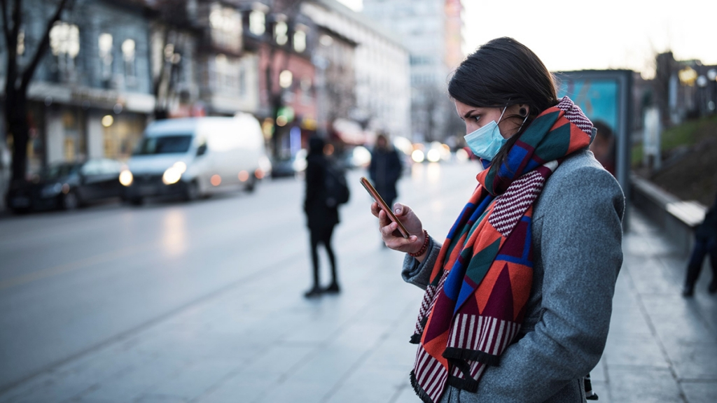 Young woman with a face mask using a smartphone. Photo: GND/iStock