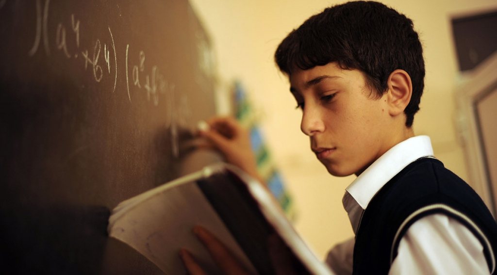 Ayyub Najarada, attends school at the Kalbajar School #56 in the Masazy settlement in Absheron Region. He is at the chalkboard, ready to answer questions.