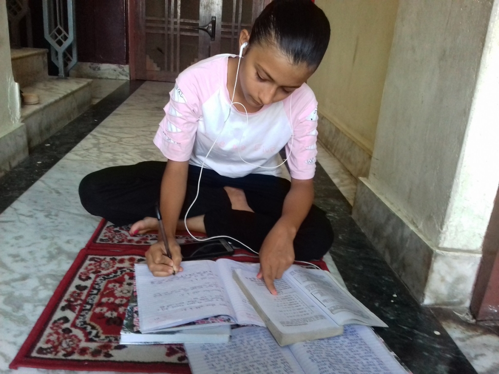 Shikshya Kafle takes notes while listening to the Radio School Program through a mobile phone.