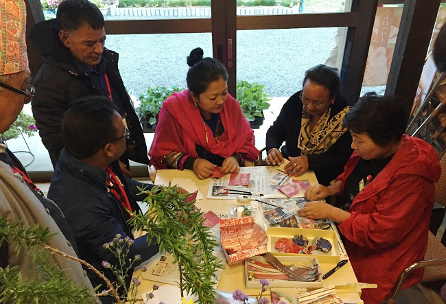 Community members from Nepal learn how to make paper jewelry crafts from Ibasho-Japan elders.