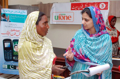 In Pakistan, Salma Riaz, right, shows Saba Bibi how to use her new cell phone to receive payments. © Muzammil Pasha/World Bank