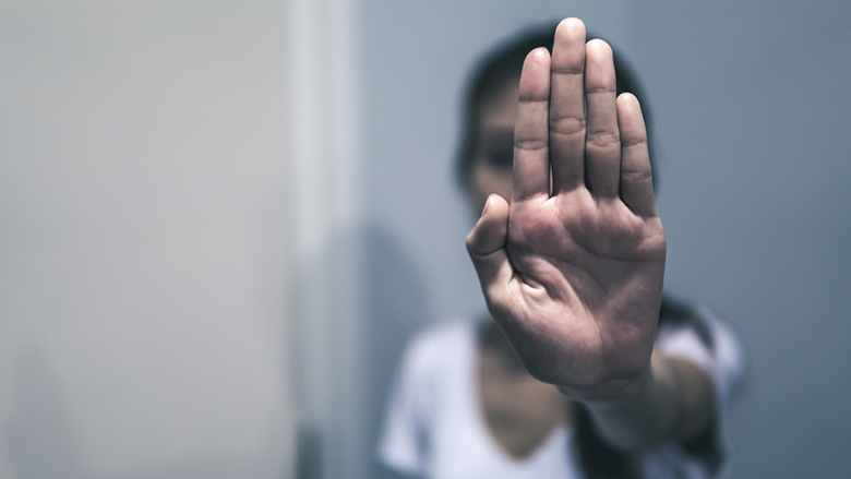 Women abused in her home holding her hand up. Stop sexual harassment against women. Violence and abuse in family relations. © Fure/Shutterstock.com