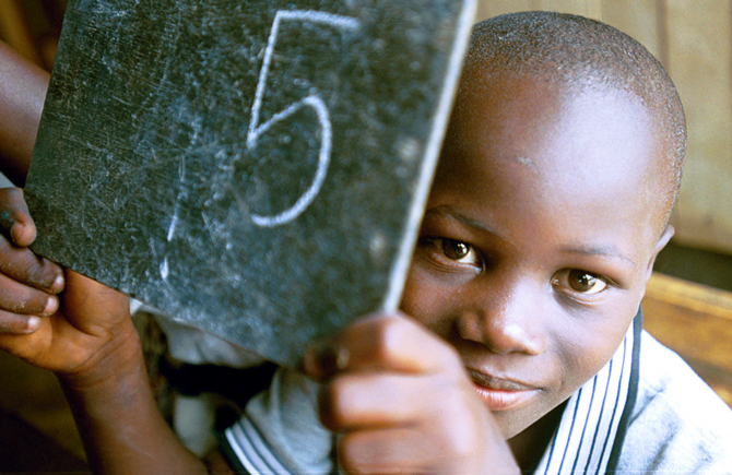 A young student in Côte d'Ivoire shows off his schoolwork. © Ami Vitale/Word Bank